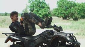 Młody człowiek kłaść przy ATV i clicing jego telefon komórkowego zdjęcie wideo