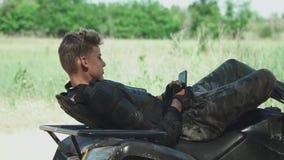 Młody człowiek kłaść przy ATV i clicing jego telefon komórkowego zbiory wideo