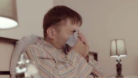 Młody człowiek kicha jego chusteczkę dmuchać jego nos i używa zbiory