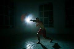 Młody człowiek kickboxing na czarnym tle Zdjęcia Royalty Free