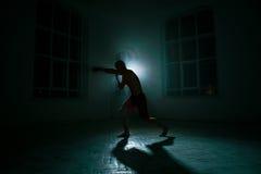 Młody człowiek kickboxing na czarnym tle Zdjęcie Stock