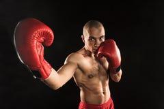 Młody człowiek kickboxing na czerni Obraz Stock