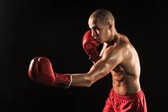 Młody człowiek kickboxing na czerni Fotografia Stock