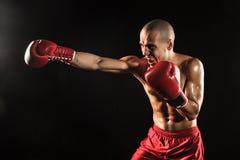 Młody człowiek kickboxing na czerni Zdjęcie Stock