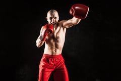 Młody człowiek kickboxing na czerni Zdjęcia Stock
