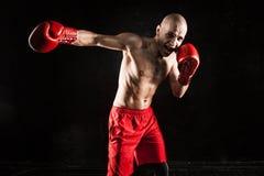 Młody człowiek kickboxing na czerni Obrazy Royalty Free