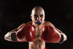 Młody człowiek kickboxing na czerni z kapą w usta Obrazy Stock
