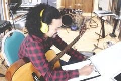 Młody człowiek komponuje piosenkę z schowkiem Obraz Royalty Free