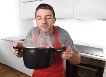 Młody człowiek kuchnia w kucbarskim fartucha mienia garnku cieszy się kulinarnego odór w domu Fotografia Royalty Free