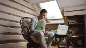 Młody człowiek liczy pieniądze laptopem zbiory