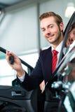 Młody człowiek lub auto handlowiec w przedstawicielstwie firmy samochodowej Obrazy Stock