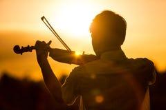 Młody człowiek lub chłopiec bawić się skrzypce przy zmierzchem Obrazy Royalty Free