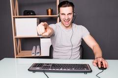 Młody człowiek lub hacker w słuchawki i eyeglasses z komputerem osobistym komputerowym bawić się gemowego, leje się wideo wskazuj zdjęcia stock