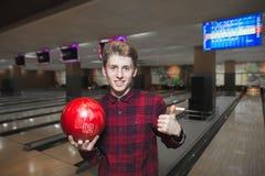 Młody człowiek lubi bawić się kręgle Młoda przystojna mężczyzna pozycja z kręgle piłką up w jego ręki i seans jego kciuk Obraz Stock