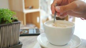 Młody Człowiek Ma Kawową przerwę, Miesza Jego weganinu Latte z łyżką i Używa telefon komórkowego, ręki zamknięty up HD zdjęcie wideo
