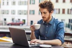 Młody człowiek ma kawową przerwę przy barem obraz stock