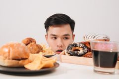 Młody człowiek ma pragnienia dla donuts, hamburger, kurczak z dłoniakami zamiast obrazy royalty free