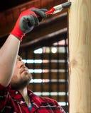 Młody człowiek maluje drewnianą powierzchnię z paintbrush obraz stock