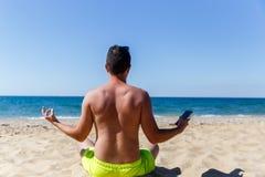 Młody człowiek medytuje siedzieć z powrotem zdjęcie stock