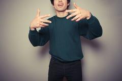 Młody człowiek myśleć go jest chłodno i gestykuluje z jego rękami Obraz Stock