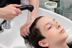 Młody człowiek myje w fryzjera ` s głowie Żeńskie fryzjera ` s ręki przygotowywają faceta ` s włosy dla ostrzyżenia obraz royalty free