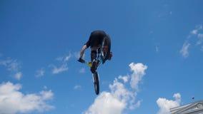 Młody człowiek na BMX roweru skokach Mężczyzna robi skrętom i sztuczkom na bmx w zwolnionego tempa niebieskiego nieba tle zbiory