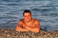 Młody człowiek na otoczak plaży Fotografia Royalty Free
