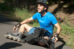 Młody człowiek na rolkowych łyżwach siedzi odpoczynkową mienie wodę Obrazy Stock