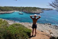 Młody człowiek na skale kontempluje seascape fotografia stock