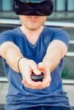 Młody człowiek naciska pulpitu operatora guzika cieszy się rzeczywistość wirtualna szkła lub 3d widowiska na miastowym budynku tl Zdjęcie Stock