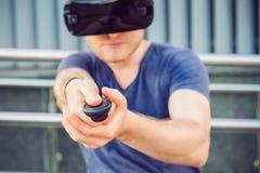 Młody człowiek naciska pulpitu operatora guzika cieszy się rzeczywistość wirtualna szkła lub 3d widowiska na miastowym budynku tl Obrazy Stock