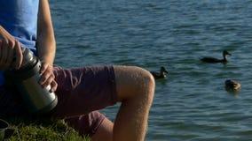 Młody człowiek nalewa herbaty w filiżance na jeziornym banku z wodą zbiory
