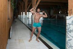 Młody Człowiek Napina mięśnie Przy Pływackim basenem Zdjęcie Stock
