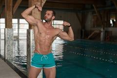 Młody Człowiek Napina mięśnie Przy Pływackim basenem Obraz Royalty Free