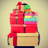 Młody człowiek niesie stos prezentów pudełka z filtrem e w kostiumu, zdjęcie royalty free
