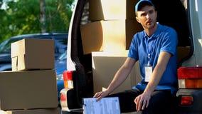 Młody człowiek od doręczeniowej usługi odpoczywa, siedzący w samochodzie dostawczym, ładować pakuneczki zdjęcia royalty free