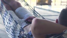 Młody człowiek odpoczywa w hamaku na lato tarasie Obsługuje chlanie na hamaku podczas gdy relaksuje na wakacje zdjęcie wideo