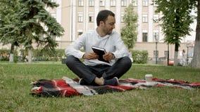 Młody człowiek odpoczywa w parku z kawą i książką iść zbiory wideo