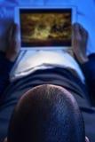 Młody człowiek ogląda film lub serie w jego pastylce w łóżku Obrazy Stock