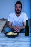 Młody człowiek ogląda film przy nighttime z układami scalonymi i piwem Zdjęcie Stock