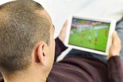 Młody człowiek ogląda mecz piłkarskiego w jego pastylce Zdjęcia Stock