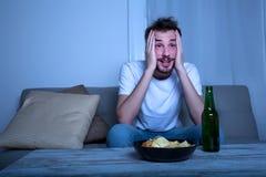 Młody człowiek ogląda TV przy nighttime z układami scalonymi i piwem Zdjęcie Stock
