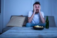 Młody człowiek ogląda TV przy nighttime z układami scalonymi i piwem Fotografia Royalty Free