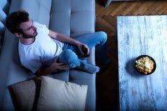 Młody człowiek ogląda TV przy nighttime z układami scalonymi i piwem Zdjęcia Royalty Free