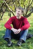 Młody człowiek ono uśmiecha się i siedzi na trawie w parku fotografia royalty free