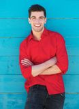 Młody człowiek ono uśmiecha się outdoors przeciw błękit ścianie Zdjęcia Royalty Free