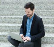 Młody człowiek ono uśmiecha się z laptopem Zdjęcia Royalty Free