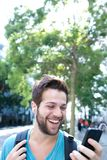 Młody człowiek ono uśmiecha się z plecakiem i patrzeje telefon komórkowego Obrazy Royalty Free