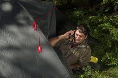 Młody człowiek opowiada na mądrze telefonie w jego namiocie Obrazy Royalty Free