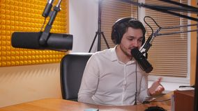 Młody człowiek opowiada na mic z hełmofonami Online radio i podcasting pojęcie zdjęcie wideo